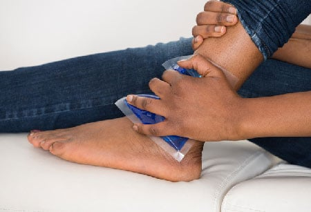 Young person with ice on ankle.